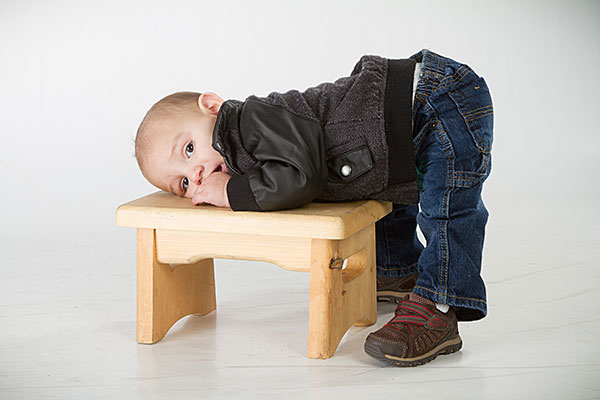 boy laying on a stool