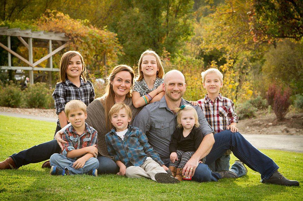 family sitting in the Ogden Botanical Gardens