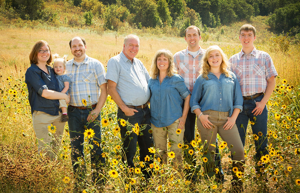family in blue in the sunflowers